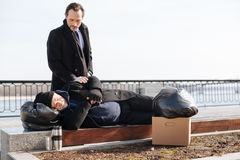 Young passersby touching sleeping man. Wake up. Homeless male person wearing black cap and coat sleeping outside on the bench keeping hands crossed on the belly Stock Image