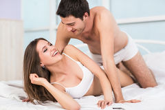 Young passionate couple in bed Stock Images