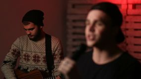Young passionate male singer performing on stage. Closeup lead singer of music group holding microphone and singing. Blurred young musician playing acoustic stock video footage