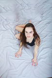 Young  passionate woman or girl lying on bed in seductive pose Royalty Free Stock Photography