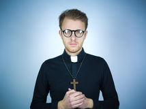 Young pastor. Portrait of a young pastor wearing a black shirt and clerical collar with a rosary and cross around his neck as he clasps his hands in prayer Royalty Free Stock Images