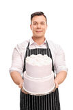 Young pastry chef holding a large cake Stock Photos
