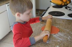 Young pastry chef making cookies. Seven year old baker having fun rolling orange cookie dough for Halloween cookies in Grandma`s kitchen Stock Photo