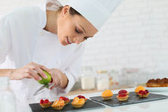 Young pastry cook preparing desert Royalty Free Stock Image