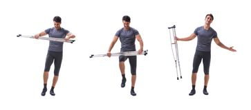 Young patient athlete sportsman suffering an injury trauma with. Crutches isolated on white royalty free stock photo