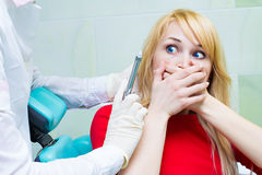 Young patient in dentist office, afraid of anesthetic injection, Stock Images