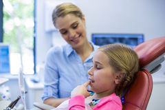 Young patient looking in the mirror at dental clinic. Young girl patient looking in the mirror at dental clinic Royalty Free Stock Photos