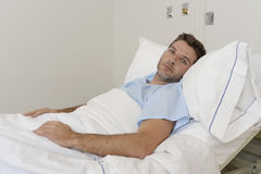 Young patient man lying at hospital bed resting tired looking sad and depressed worried. About medical condition suffering disease feeling sick in health care Royalty Free Stock Images