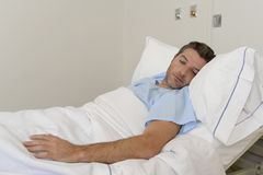 Young patient man lying at hospital bed resting tired looking sad and depressed worried. About medical condition suffering disease feeling sick in health care Royalty Free Stock Photos