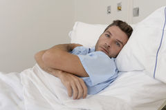 Young patient man lying at hospital bed resting tired looking sad and depressed worried. About medical condition suffering disease feeling sick in health care Royalty Free Stock Image