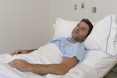 Young patient man lying at hospital bed resting tired looking sad and depressed worried. About medical condition suffering disease feeling sick in health care Stock Photography