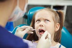Young patient sits at dentist chair and feels pain. Young patient with frowning brows and ginger hair sits at dentist chair and feels pain while doctor performs Stock Image