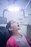 Young patient sitting on dentists chair with mouth open Stock Image