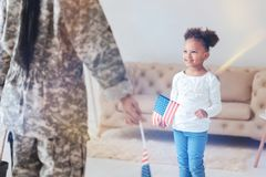 Cheerful pretty girl holding a US flag. Young patriot. Cheerful positive pretty girl looking at her mother and smiling while holding a US flag royalty free stock image