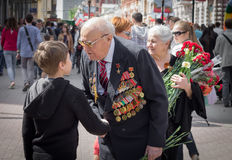 Young patriot speaks with old veteran of World War II. On the chest of veteran many military awards. Behind the veteran his wife holds big bouquet of stock images