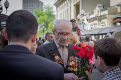 Young patriot speaks with old veteran of World War II. On the chest of veteran many military awards. Behind the veteran his wife holds big bouquet of royalty free stock photos