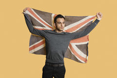 Young patriotic man lifting British flag over colored background Stock Photography