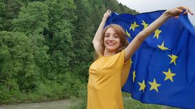 Young patriotic woman is holding a banner of European Union flag the over green forest background during spring day. HD stock video footage
