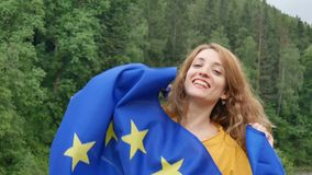 Young patriotic woman holding flag of the European Union on green forest background during spring day outdoors while. Celebrating visa-free regime, HD stock video