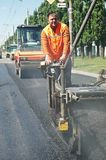 Young paver worker at asphalting. Young builder on Asphalting paver machine during Road street repairing works Stock Photo