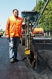 Young paver worker at asphalting. Young builder on Asphalting paver machine during Road street repairing works Royalty Free Stock Image