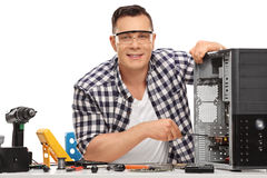 Young PC technician repairing computer. Young PC technician repairing a broken desktop computer and looking at the camera isolated on white background Stock Photo