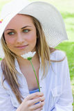 Young peaceful girl holding a white flower in a park Stock Images