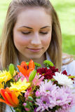 Young peaceful woman smelling a bunch of flowers while closing h Royalty Free Stock Photo