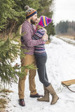 Young peaople are kissing in winter forest Royalty Free Stock Photos