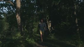 A young peasant walking in the woods. Hiker hiking in forest at sunset. Active lifestyle. Wearing a checkered shirt and