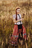 Young peasant woman, dressed in Hungarian national costume, posing over nature background Stock Photo