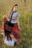 Young peasant woman, dressed in Hungarian national costume, posing over nature background Stock Photography