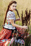 Young peasant woman, dressed in Hungarian national costume, posing over nature background Stock Image