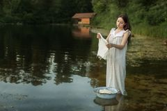 Woman washing clothes in the river stock images