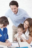 Pediatrician and family. Young pediatrician doctor talking with girl and her parents stock photos