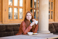 Young pencive lady drinking coffee in a street cafe Royalty Free Stock Photo