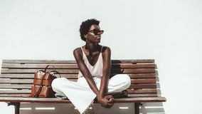 Black girl on the wooden bench royalty free stock photo