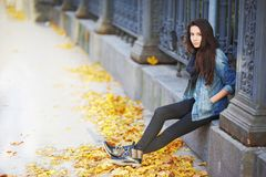 Young pensive brunette girl sitting on a concrete curb around a beautiful iron fence, under the feet of yellow autumn maple leaves Royalty Free Stock Images