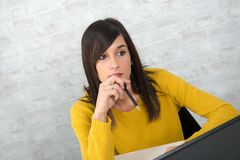 Young pensive brunette woman in the office Royalty Free Stock Photography