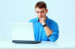 Young pensive businessman in blue shirt sitting at the table with laptop Royalty Free Stock Photos