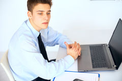 Young pensive businessman at his workplace in office Royalty Free Stock Photography
