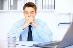 Young pensive businessman in office Stock Photos