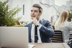 Young pensive businessman sitting next to laptop and touching his chick. royalty free stock images