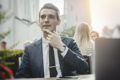 Young pensive businessman sitting next to laptop and touching his chick. royalty free stock photography