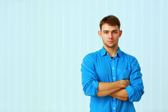 Young pensive businessman standing with arms folded Royalty Free Stock Image