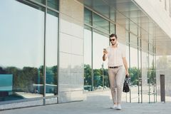 Confident thoughtful businessman using phone outdoors Royalty Free Stock Photo