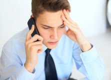Young pensive businessman talking on cell phone Royalty Free Stock Images