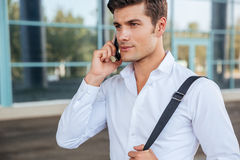 Young pensive businessman talking on the phone outdoors Stock Photos