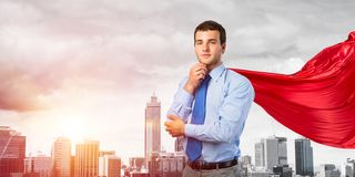 Concept of power and sucess with businessman superhero in big city. Young pensive businessman wearing red cape against modern city background royalty free stock images