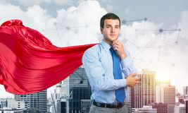 Concept of power and sucess with businessman superhero in big city. Young pensive businessman wearing red cape against modern city background stock image